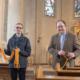 Pfarrer Peter Wohs und Küster Andreas Ataman beim Absperren der Kirchenbänke